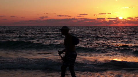 Silhouette of elderly man walking on the beach at sunset. Hiking Footage