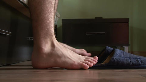 Male feet getting out of bed, put on slippers Footage