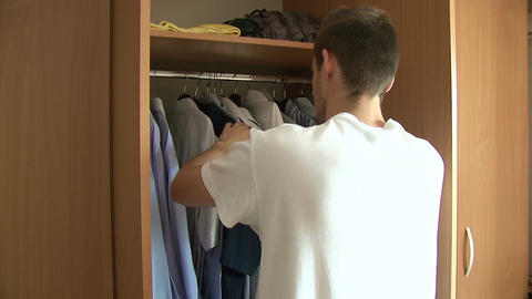 Man choosing shirt from wardrobe Footage