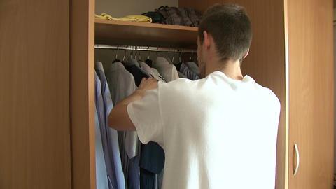 Man choosing shirt from wardrobe Footage