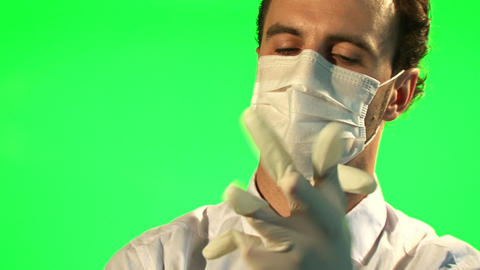 Doctor puts on mask and surgical gloves - green screen Live Action