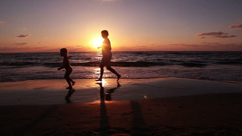 Mother and daughter running along the seashore at sunset Footage