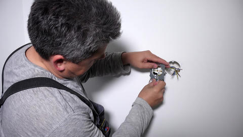 Man with screwdriver screw electrical outlet on wall Live Action
