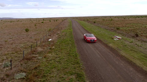 Aerial view of red car reverse on country road Live Action