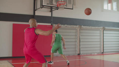 Two athletes training basketball skills indoors Live Action