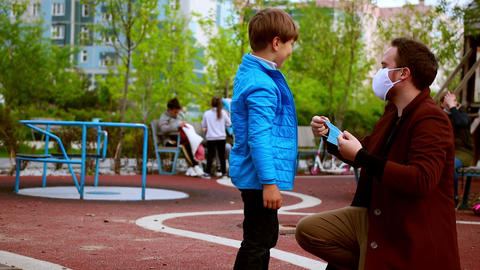 Young man and little boy walking on the playground - caring man put on a medical Live Action
