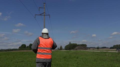 Electrical Engineer talking on smartphone under high-voltage lines Footage