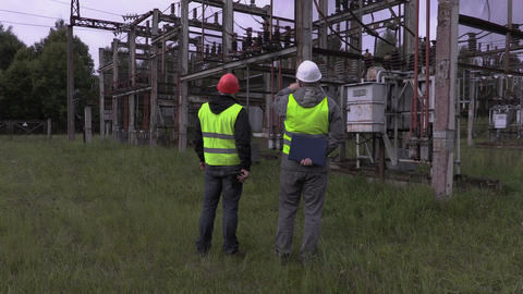 Electricians talking in electrical substation Live Action