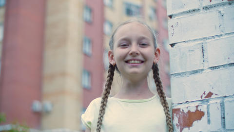 Playful girl teenager laughing on brick wall background in residential district Live Action