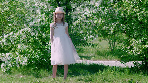 Attractive girl in white summer dress and hat on blooming fruit trees in orchard Live Action