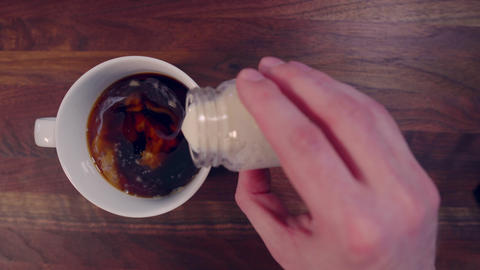 Pouring cream into coffee cup and stirring drink Live Action