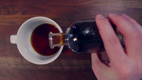 Pouring cold brew coffee into coffee cup overhead view Live Action