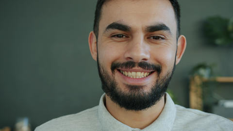 Close-up portrait of attractive bearded Arab man smiling indoors at home Live Action