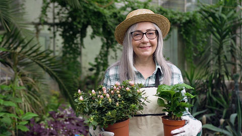 Friendly joyful grey-haired senior female gardener looking at camera with two Live Action