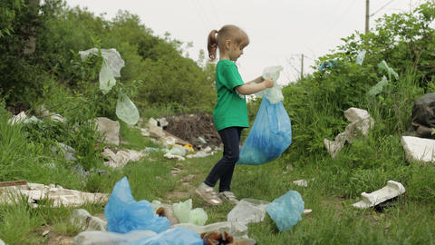 Volunteer girl cleaning up dirty park from plastic bags, bottles. Reduce trash Live Action