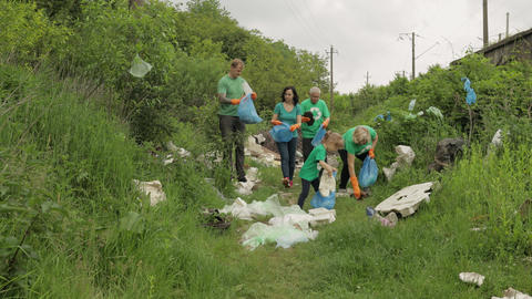 Volunteer team cleaning up dirty park from plastic bags, bottles. Reduce trash Live Action