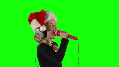 Emotional girl with microphone singing song with headphones. Green screen Live Action