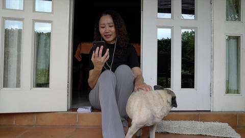 Woman chatting on her cellphone with earphones. Home setting with pug dog Live Action