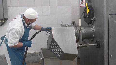 the employee washes the equipment with water from a hose at the enterprise Live Action