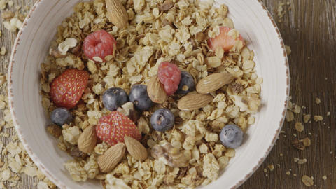 Top view of preparing healthy breakfast from falling granola, fr Live Action