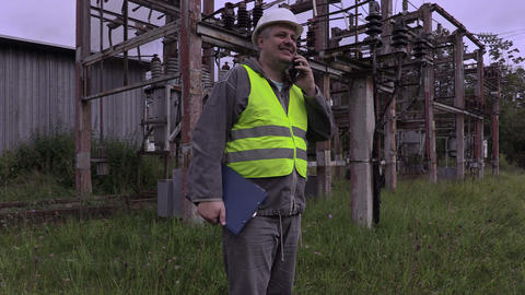Electrician with smartphone and documentation walking in substation Live Action