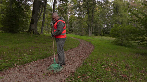 Park employee walking and start collect leaves in park Live Action