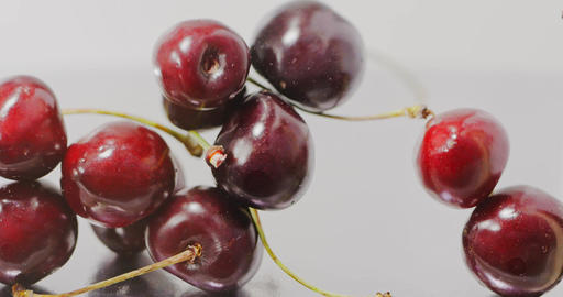 Close-up of a ripe red large cherries slowly falls and fills the screen. Slow Live Action