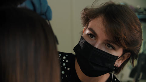 Young woman cosmetologist in black mask brushing eyebrows of a young woman Live Action