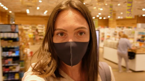 Woman in protective mask in shop Live Action