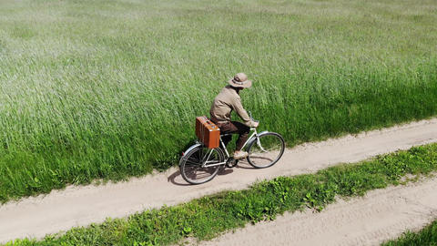 man riding on bicycle by country road in a green field, holding suitcase in a Live Action