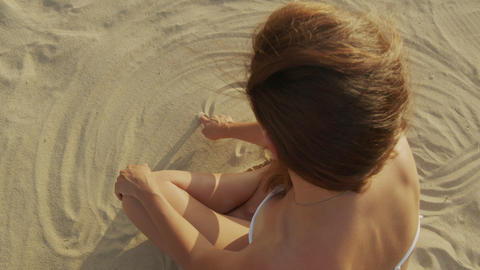 Pregnant girl sitting on the beach in the sand draws a heart symbol in the sand Live Action