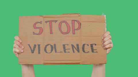 Hands holding cardboard with stop violence sign on green chromakey background Live Action