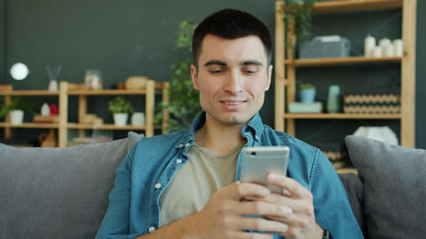 Joyful man using smartphone texting having fun smiling in house alone Live Action