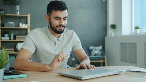 Tired freelancer Arab man working with laptop in apartment then leaving quitting Live Action