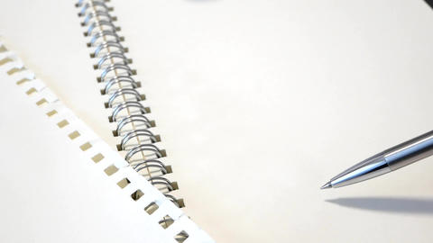 Open notebook and pen. Move the pen. Think of plans, ideas, etc Live Action