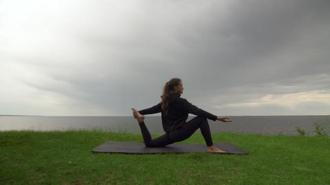 Young fit woman practice yoga on coast near the lake or sea. Woman doing One Live Action