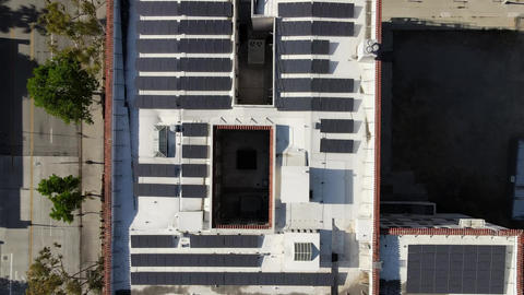 Solar installation project on commercial building roof, California, aerial Live Action