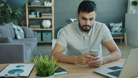 Cheerful Arab man using smartphone touching screen in apartment at desk Live Action