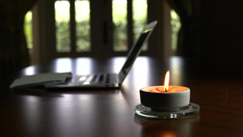 Candlelight on table with computer laptop at the background. Home setting Live Action