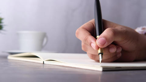 Close up of women hand with pen writing on a diary Live Action