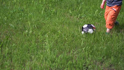 child playing soccer with a ball in the long grass, close-up of the foot and ball, tracking camera Live Action