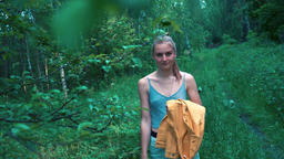 Beautiful young girl walking alone on a path in a dense forest, slow motion Live Action