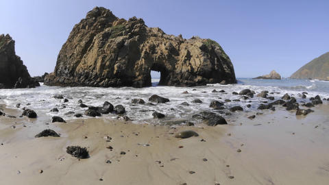 Low angle time lapse of waves breaking through a rock at Pfeiffer Beach in Big Sur, California Footage