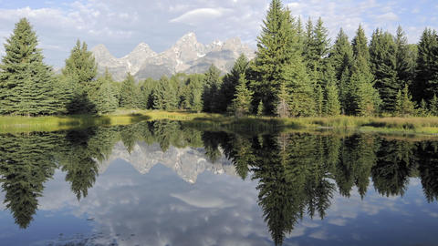 Time lapse motion of clouds, mountains and forest reflecting at Schwabacher Landing in Grand Teton N Footage