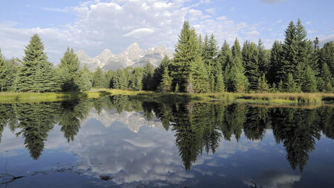 Slow time lapse of clouds, mountains and forest reflecting at Schwabacher Landing in Grand Teton Nat Footage