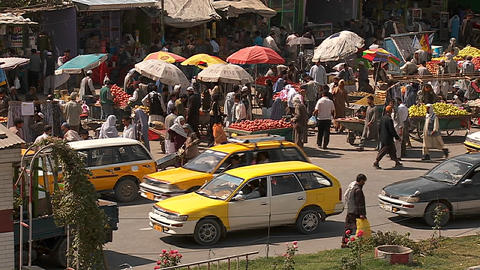 Taxis and vehicle traffic near a busy fruit market in Kabul, Afghanistan Footage