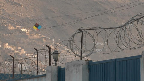 Razor wire and kites flying against a hillside in Kabul,... Stock Video Footage