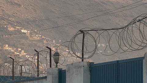 Razor wire and kites flying against a hillside in Kabul, Afghanistan Footage