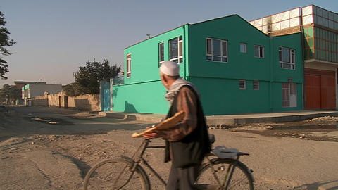 A lonely abandoned neighborhood in Kabul, Afghanistan with a man on a bicycle passing Footage