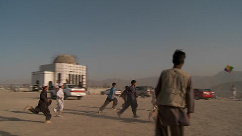 Kids chase and play with kites in an empty lot in kabul, Afghanistan Footage